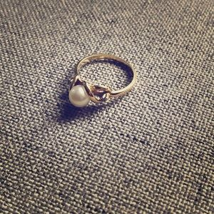 Gold ring, pearl center, two  diamonds on side.